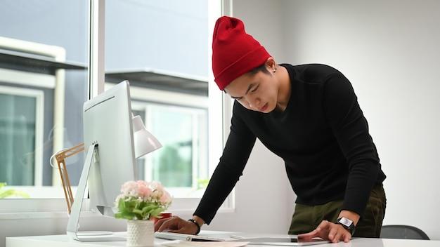 Portret mężczyzny grafik w czerwonym wełnianym kapeluszu pracującym w biurze kreatywnym