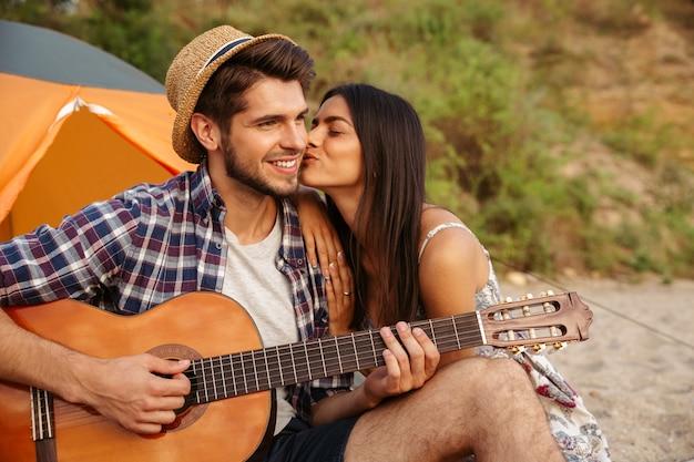 Portret mężczyzny grającego na gitarze dla swojej dziewczyny siedzącej w namiocie kempingowym na plaży
