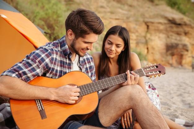 Portret mężczyzny grającego na gitarze dla swojej dziewczyny siedzącej w namiocie kempingowym