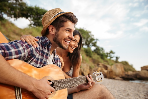 Portret Mężczyzny Grającego Na Gitarze Dla Swojej Dziewczyny Siedzącej W Namiocie Kempingowym Premium Zdjęcia