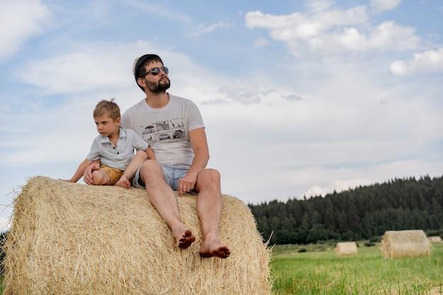 Portret mężczyzny i jego małego synka siedzących na okrągłym stogu siana w zielonym polu w słoneczny letni dzień
