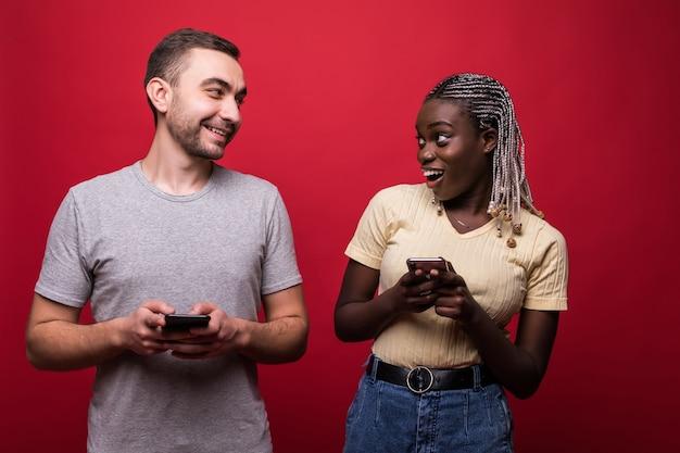 Portret mężczyzny i kobiety rasy mieszanej marszcząc brwi i zerkając na siebie telefony komórkowe odizolowane na czerwonym tle