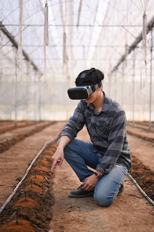 Portret mężczyzny inteligentny rolnik siedzi w szklarni i nosi technologię okularów rzeczywistości wizualnej.