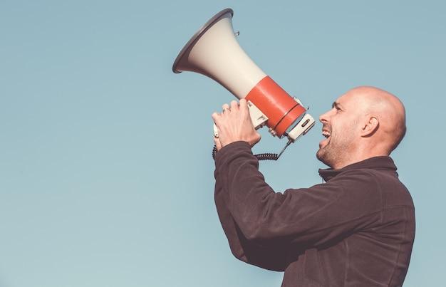 Portret mężczyzny krzyczącego, krzyczącego do megafonu
