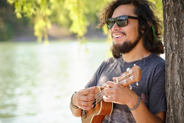 Portret mężczyzny łacińskiego z okulary grające na ukulele i śpiewa z uśmiechem.