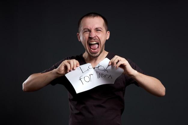 Portret mężczyzny łzawiącego napis na papierze szuka pracy