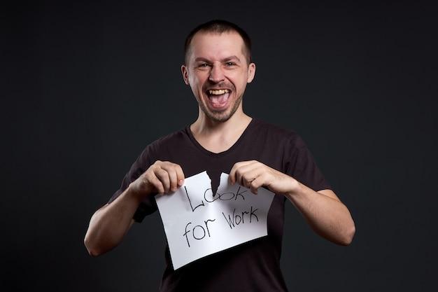 Portret mężczyzny łzawienie napis na papierze szuka pracy