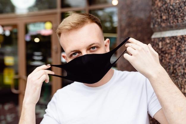 Portret mężczyzny. mężczyzna w czarnej masce. kwarantanna w mieście.