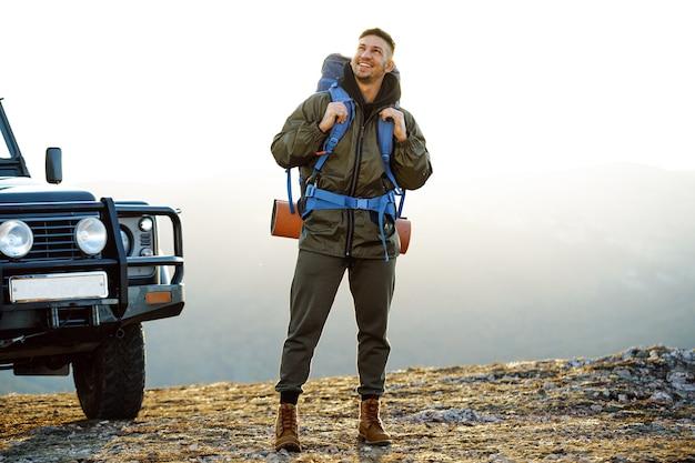 Portret mężczyzny młodego podróżnika w sprzęcie turystycznym stojącego w pobliżu jego samochodu terenowego o świcie