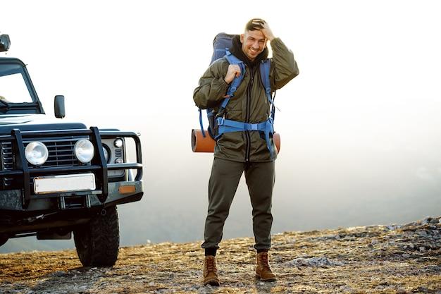 Portret mężczyzny młodego podróżnika w sprzęcie turystycznym stojącego w pobliżu jego samochodu terenowego