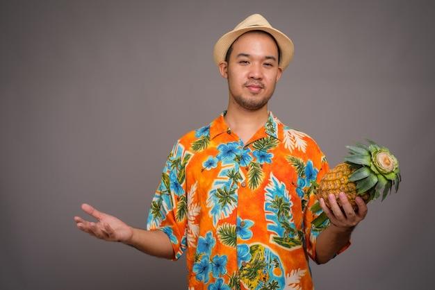 Portret mężczyzny młodego turysty azjatyckich gospodarstwa ananasem