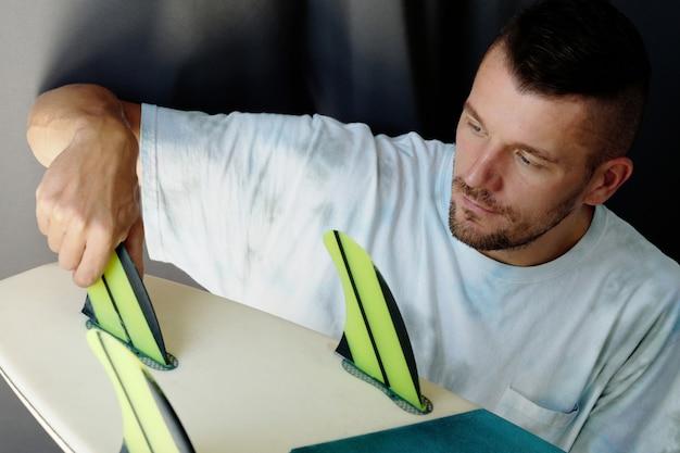 Portret mężczyzny mocującego płetwy na spodzie deski surfingowej w domu.