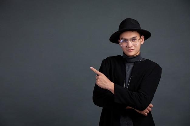Portret mężczyzny model palcem wskazującym i uśmiechając się na ciemnej ścianie