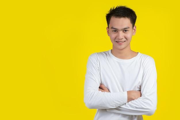 Portret mężczyzny model skrzyżował ramiona i uśmiechał się na żółtej ścianie