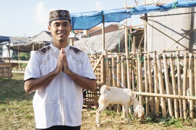 Portret mężczyzny muzułmańskiego stojącego przed farmą kóz. koncepcja poświęcenia eid adha