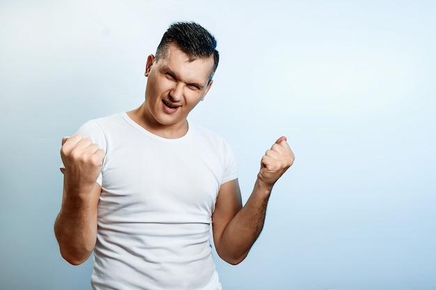 Portret mężczyzny na jasnym tle, pokazuje gest rękami rock n roll.