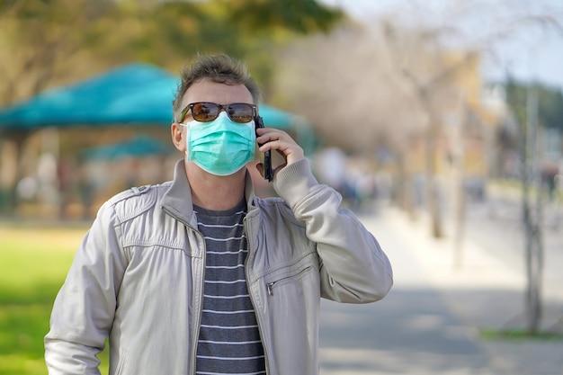 Portret mężczyzny na ulicy w maski medyczne i mówi przez telefon. atrakcyjny nieszczęśliwy model z grypą na zewnątrz. nieszczęśliwy człowiek z grypą na zewnątrz.