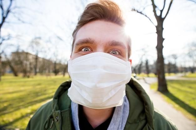 Portret mężczyzny noszącego maskę medyczną w miejskim parku publicznym