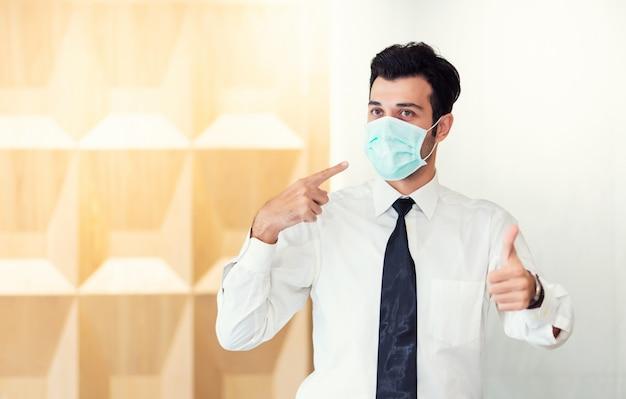 Portret mężczyzny noszącego maskę ochronną w celu ochrony przed zanieczyszczeniem powietrza, świadomością środowiskową i ogniskiem koronawirusa covid-19