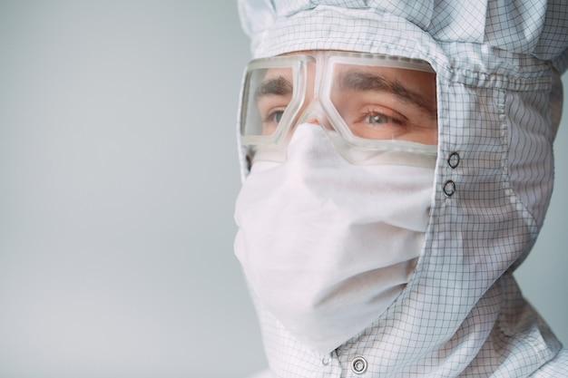 Portret mężczyzny o europejskim wyglądzie w masce medycznej, okularach ochronnych i kombinezonie chemicznym.