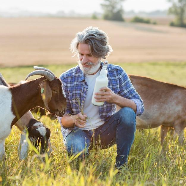 Portret mężczyzny obok kóz z butelką mleka