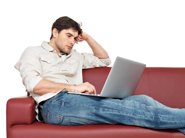 Portret mężczyzny odpoczynku z laptopem siedzi na kanapie, na białym tle.