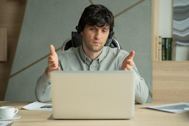 Portret mężczyzny patrzącego na mówienie do kamery podczas rozmowy wideo z biura