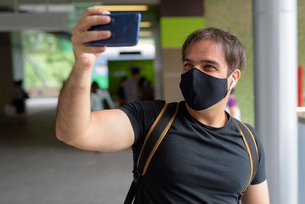 Portret mężczyzny perskiego turysty z maską do ochrony przed wybuchem koronawirusa na stacji kolejowej na niebie