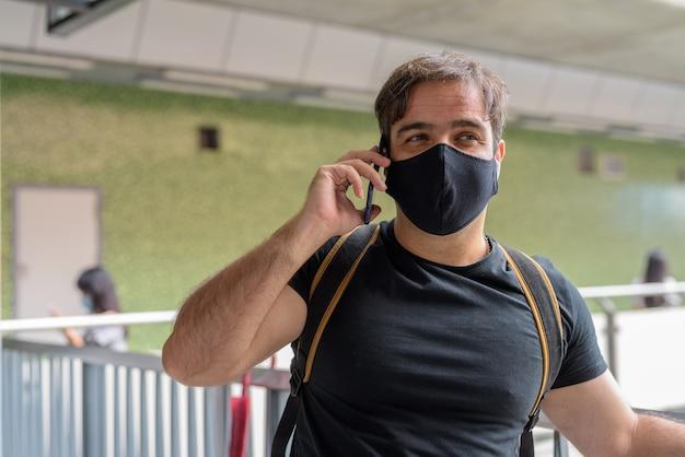 Portret mężczyzny perskiego turysty z maską do ochrony przed wybuchem wirusa koronowego na dworcu nieba