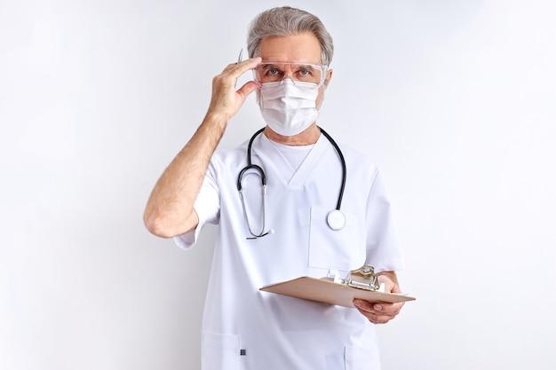 Portret mężczyzny pewność, starszy lekarz dostosowując okulary, w studio z białym tłem. szary