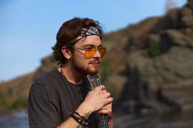 Portret mężczyzny podróżnika, który siedzi opierając się na ukulele w naturze nad jeziorem wysokiej jakości zdjęcie