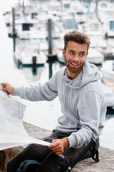Portret mężczyzny podróżującego sprawdzającego mapę