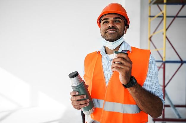 Portret mężczyzny pracownika w odzieży roboczej na przerwie, napij się kawy i odpocznij