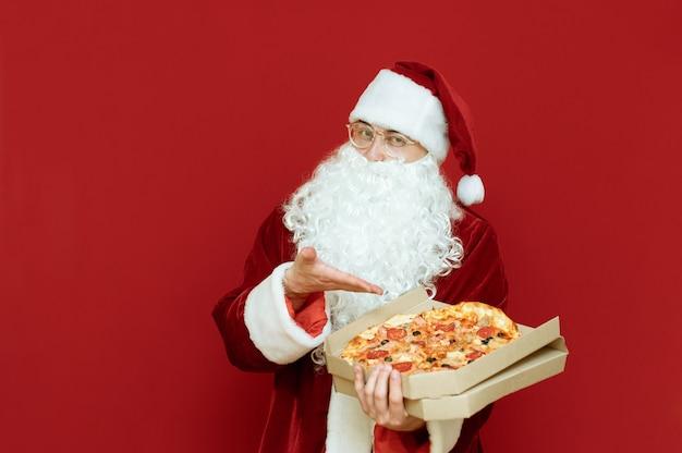 Portret mężczyzny przebranego za świętego mikołaja trzymającego pizzę