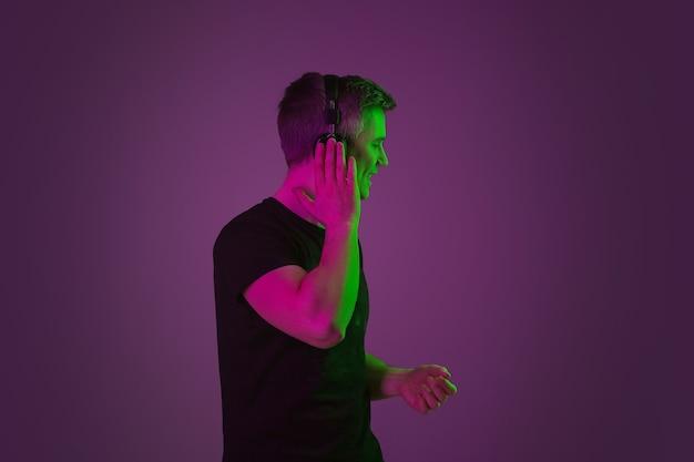 Portret mężczyzny rasy kaukaskiej na fioletowym studio w świetle neonu.