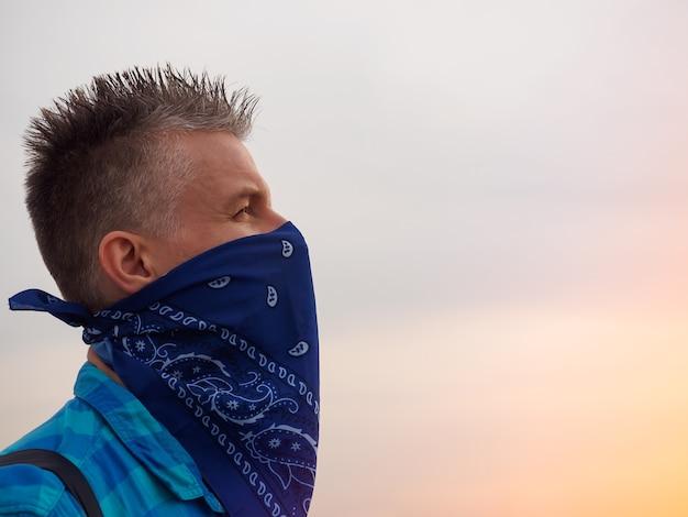 Portret mężczyzny rasy kaukaskiej w promieniach zachodzącego słońca. jego twarz była zakryta niebieską bandaną, ubrany w kraciastą niebieską koszulę. mężczyzna ma czarny plecak. siwe włosy ułożone do góry.