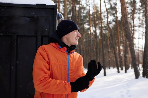 Portret mężczyzny rozciągającego się w parku w piękny śnieżny zimowy dzień