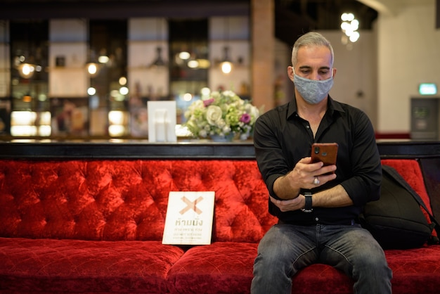 Portret mężczyzny siedzącego, dystans społeczny i przy użyciu telefonu komórkowego