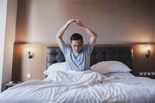 Portret mężczyzny siedzącego i wyciągającego ręce w łóżku, gdy nie śpi