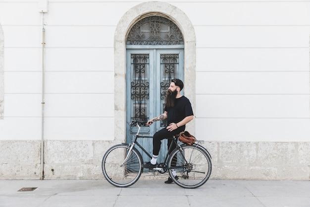 Portret mężczyzny siedzącego na rowerze przed niebieskim drzwi
