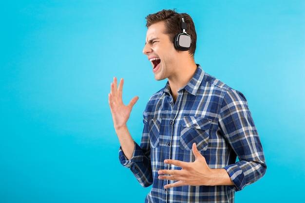 Portret mężczyzny, słuchanie muzyki na słuchawkach bezprzewodowych, zabawy na niebiesko
