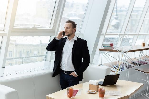 Portret mężczyzny stojącego w nowoczesnym wnętrzu i wzywającego telefon komórkowy obok stołu.