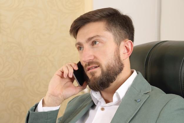 Portret mężczyzny sukcesu w biznesie z telefonem komórkowym w biurze