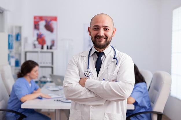 Portret mężczyzny terapeuty pediatry ze stetoskopem patrzącym w przód stojący w sali konferencyjnej