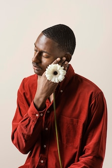 Portret mężczyzny trzymającego kwiat