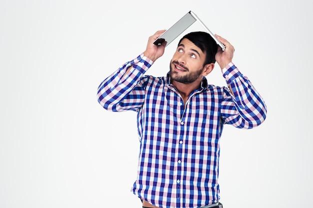 Portret mężczyzny trzymającego laptopa na głowie jak dach domu na białym tle na białej ścianie