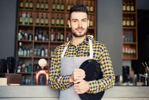 Portret mężczyzny trzymającego tacę w barze