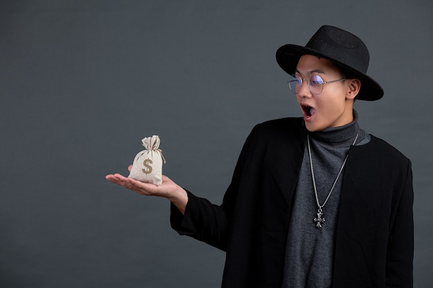 Portret mężczyzny trzymającego worek monety na ciemnej ścianie