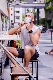 Portret mężczyzny w białej masce medycznej na centralnym placu w mieście siedzi na krześle w van cafe