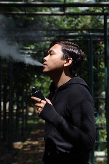 Portret mężczyzny w czarnym vape palenia